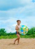 El muchacho feliz juega una playa Foto de archivo