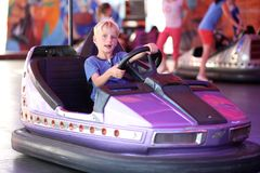 El muchacho feliz monta el coche eléctrico en parque de atracciones Fotos de archivo