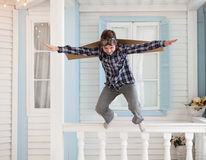 El muchacho feliz salta con las cajas de cartón de alas Imagenes de archivo