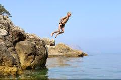 El muchacho feliz salta de roca en el mar Fotos de archivo libres de regalías