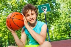 El muchacho feliz se sienta en el patio, bola de los controles cerca de la cara Fotografía de archivo