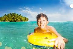 El muchacho feliz sonriente en tablero del cuerpo nada en el mar Fotografía de archivo libre de regalías
