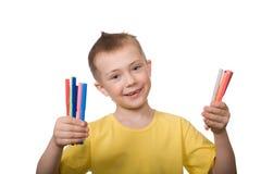 El muchacho feliz sostiene etiquetas de plástico coloridas Fotografía de archivo libre de regalías