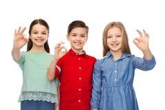 El muchacho feliz y la muchacha que muestran la mano aceptable firman Imagenes de archivo