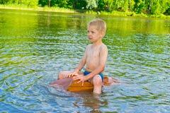 El muchacho flota en el río Imagenes de archivo