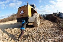 El muchacho fuerte empuja un rodillo Imagen de archivo libre de regalías