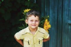 El muchacho gay hermoso está sosteniendo un girasol de las flores Foto de archivo libre de regalías