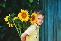 El muchacho gay hermoso está sosteniendo un girasol de las flores Imagen de archivo libre de regalías