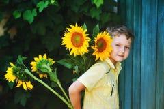 El muchacho gay hermoso está sosteniendo un girasol de las flores Foto de archivo