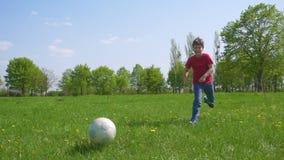 El muchacho golpeó la bola en el playfield verde, cámara lenta almacen de metraje de vídeo