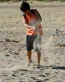 El muchacho golpea una pelota de golf en la playa Foto de archivo