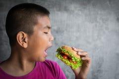 El muchacho gordo asiático del retrato goza el comer con la hamburguesa Imágenes de archivo libres de regalías