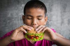 El muchacho gordo asiático del retrato goza el comer con la hamburguesa Imagen de archivo