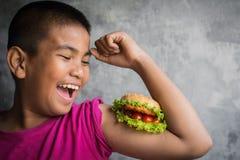 El muchacho gordo asiático del retrato goza el comer con la hamburguesa Foto de archivo libre de regalías