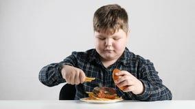 El muchacho gordo joven añade las fritadas a los fps de la hamburguesa 50
