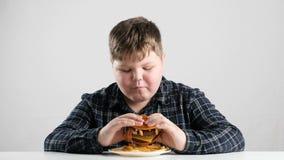 El muchacho gordo joven come fps grandes de una hamburguesa 50