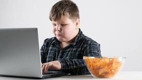 El muchacho gordo joven come microprocesadores y y juegos en fps de un ordenador portátil 50 almacen de video