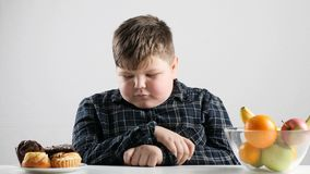 El muchacho gordo joven elige las tortas en vez de las frutas 50 fps