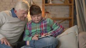 El muchacho gordo joven se está sentando con su abuelo en el sofá y está jugando en la tableta La diferencia de generaciones almacen de metraje de vídeo
