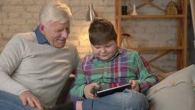 El muchacho gordo joven se está sentando con su abuelo en el sofá y está jugando en la tableta La diferencia de generaciones almacen de video