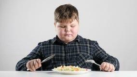 El muchacho gordo joven se preparó para comer fps de la ensalada 50