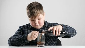 El muchacho gordo joven vierte soda en fps de un vidrio 50 almacen de video