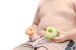 El muchacho gordo obeso está sosteniendo el buñuelo aislado foto de archivo libre de regalías