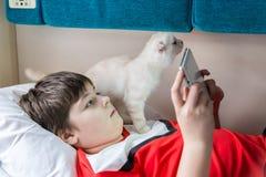El muchacho goza de la tableta en el tren, gatito que se sienta cerca Fotografía de archivo libre de regalías