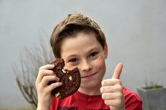 El muchacho goza de los pasteles Imagen de archivo