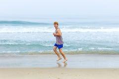 El muchacho goza el activar a lo largo de la playa foto de archivo