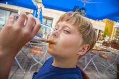 El muchacho goza el beber en el restaurante al aire libre Fotos de archivo