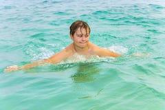El muchacho goza el nadar en el océano Imagen de archivo libre de regalías