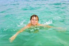El muchacho goza el nadar en el océano Foto de archivo libre de regalías