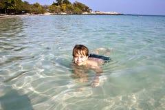 El muchacho goza el nadar en el océano tropical Imagen de archivo