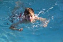 El muchacho goza el nadar en la piscina Foto de archivo