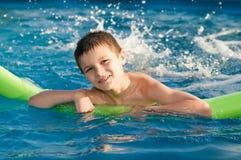 El muchacho goza en la piscina Fotografía de archivo