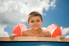 El muchacho goza en la piscina Imagen de archivo