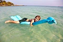 El muchacho goza para derivar en un colchón inflable en el océano Imagenes de archivo