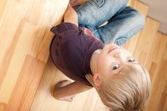 El muchacho graciosamente se sienta en una escalera Imagen de archivo