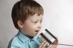 El muchacho habla en teléfono de la poder de estaño foto de archivo