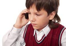 El muchacho habla en un phon móvil Imagenes de archivo