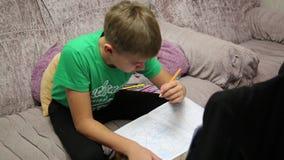 El muchacho hace la asignación de escuela almacen de metraje de vídeo