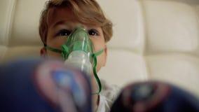 El muchacho hace la inhalación mientras que se sienta en la cama el niño inhala el vapor almacen de video