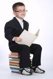 El muchacho hace la preparación que se sienta en la pila de libros Fotos de archivo libres de regalías