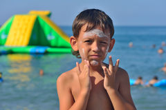 El muchacho hace la protección solar en cara Fotografía de archivo