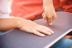 El muchacho hace los agujeros de perno en el griptape en un monopatín Fotos de archivo