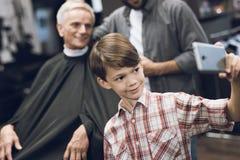 El muchacho hace el selfie en un smartphone con dos más viejos hombres en barbería Imágenes de archivo libres de regalías