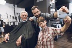 El muchacho hace el selfie en un smartphone con dos más viejos hombres en barbería Fotos de archivo