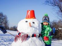 El muchacho hace un muñeco de nieve Imagenes de archivo
