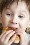 El muchacho hambriento come con la boca abierta Fotos de archivo